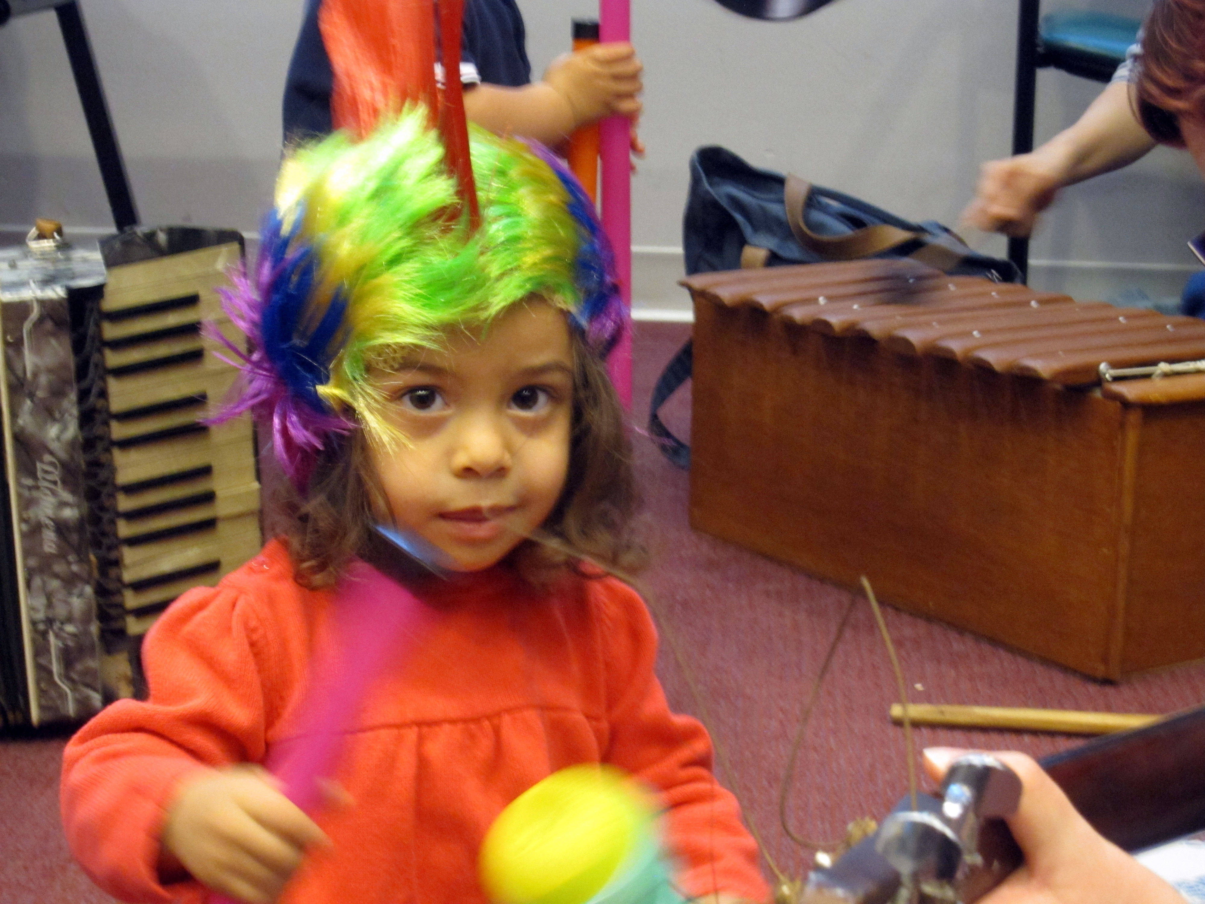 A toddler wears a rainbow-colored mohawk wig and waves around her baton.