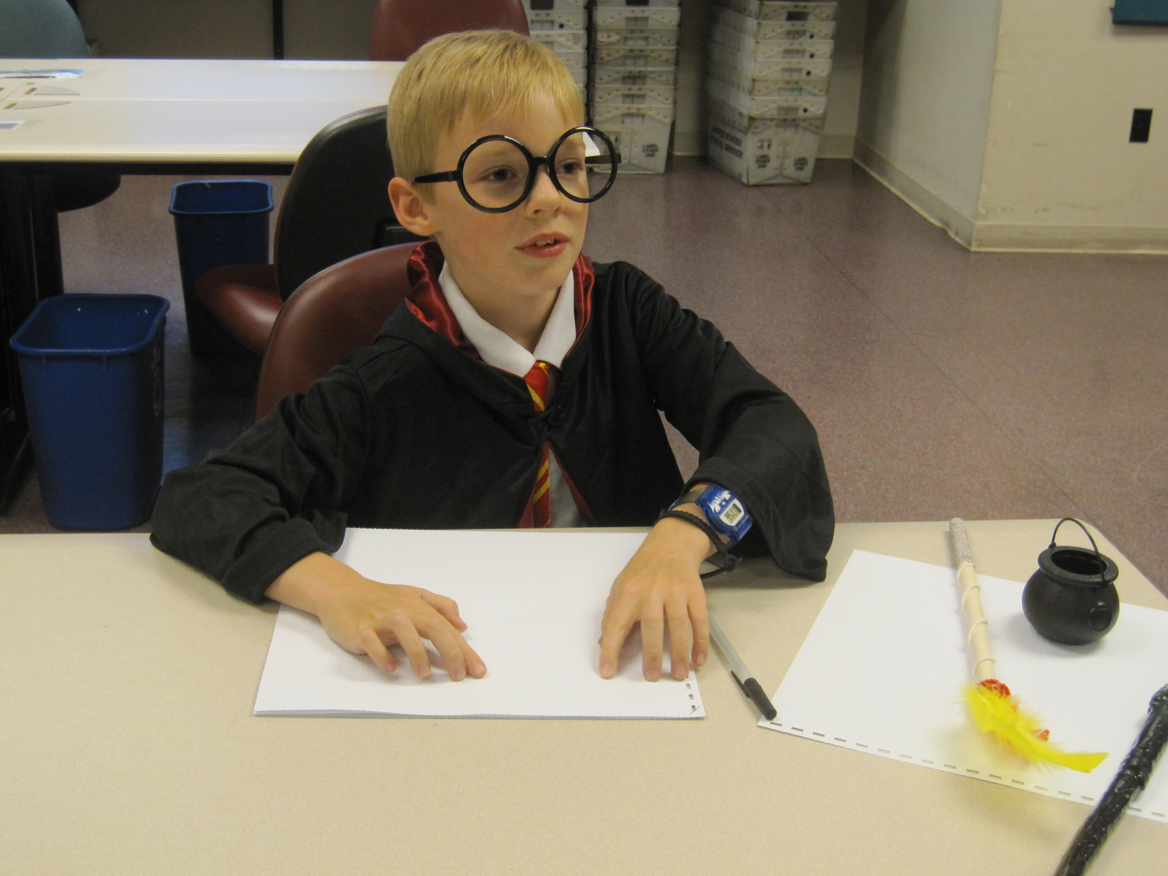 A young patron in Harry Potter glasses and robes reads a braille transcription of the Scavenger Hunt list.