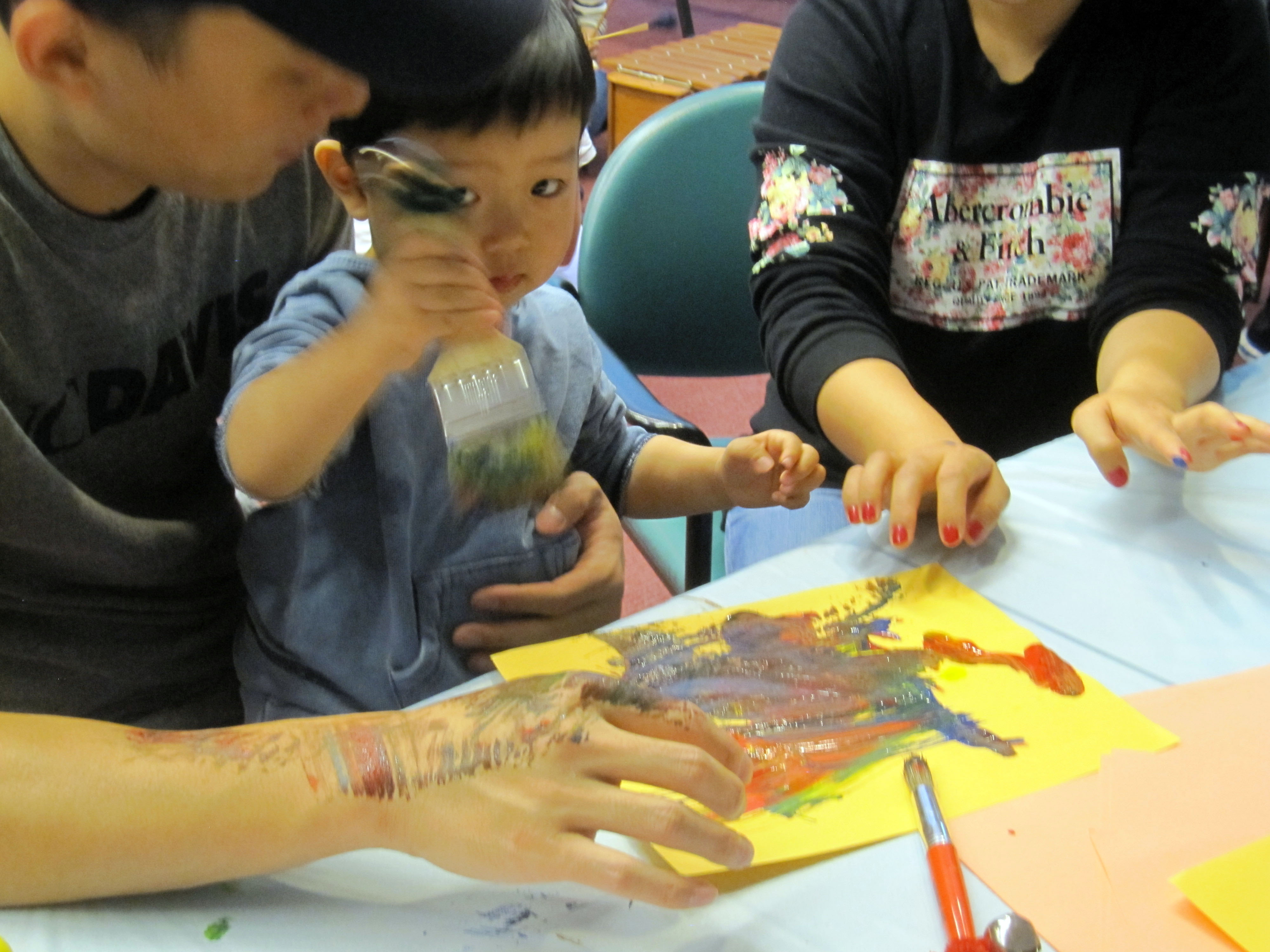 Young children paint with primary colors. Their paint brushes have different size bells attached, ringing with each stroke.
