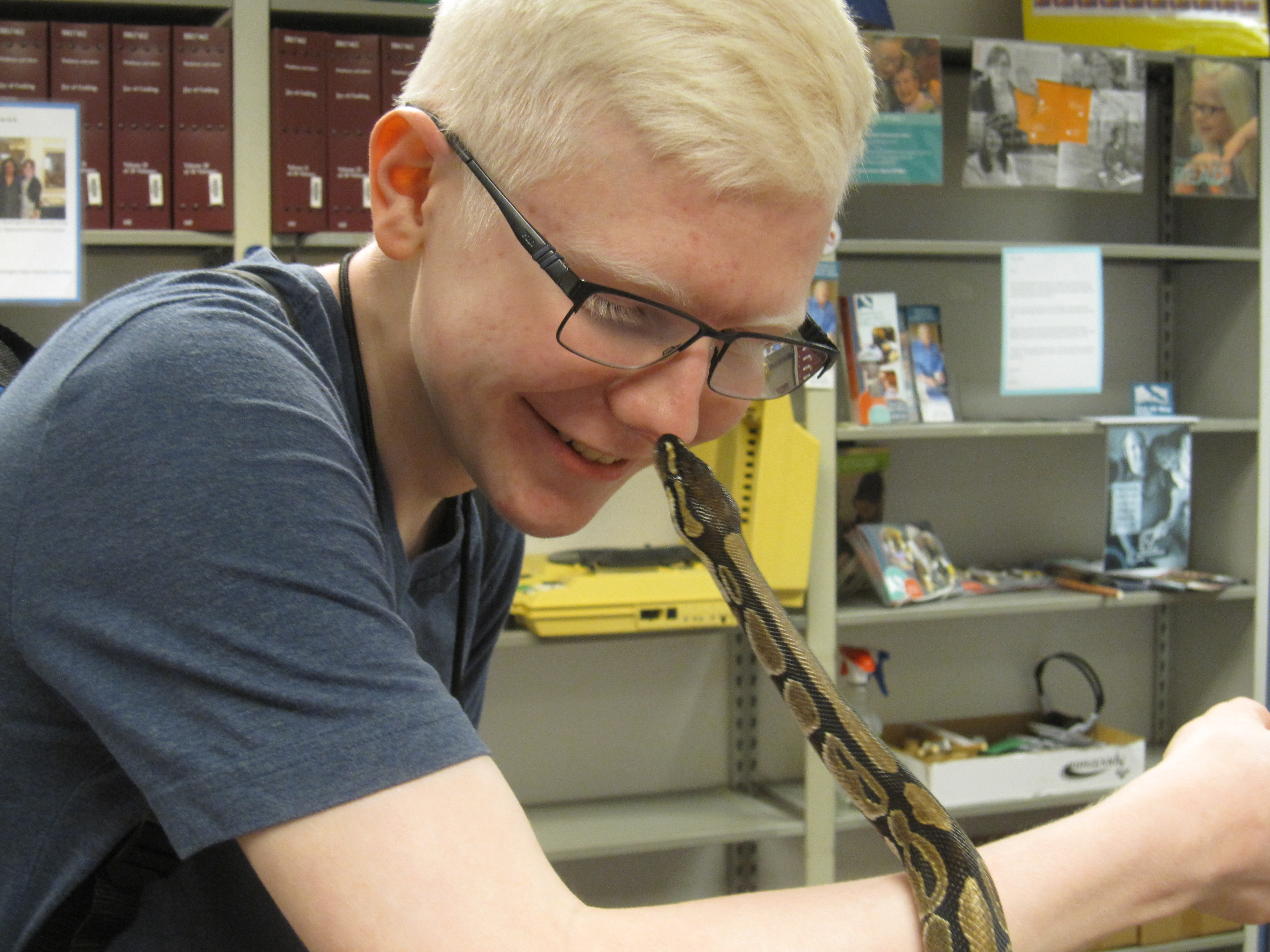 A teen patron smiles as a snake touches noses with him.