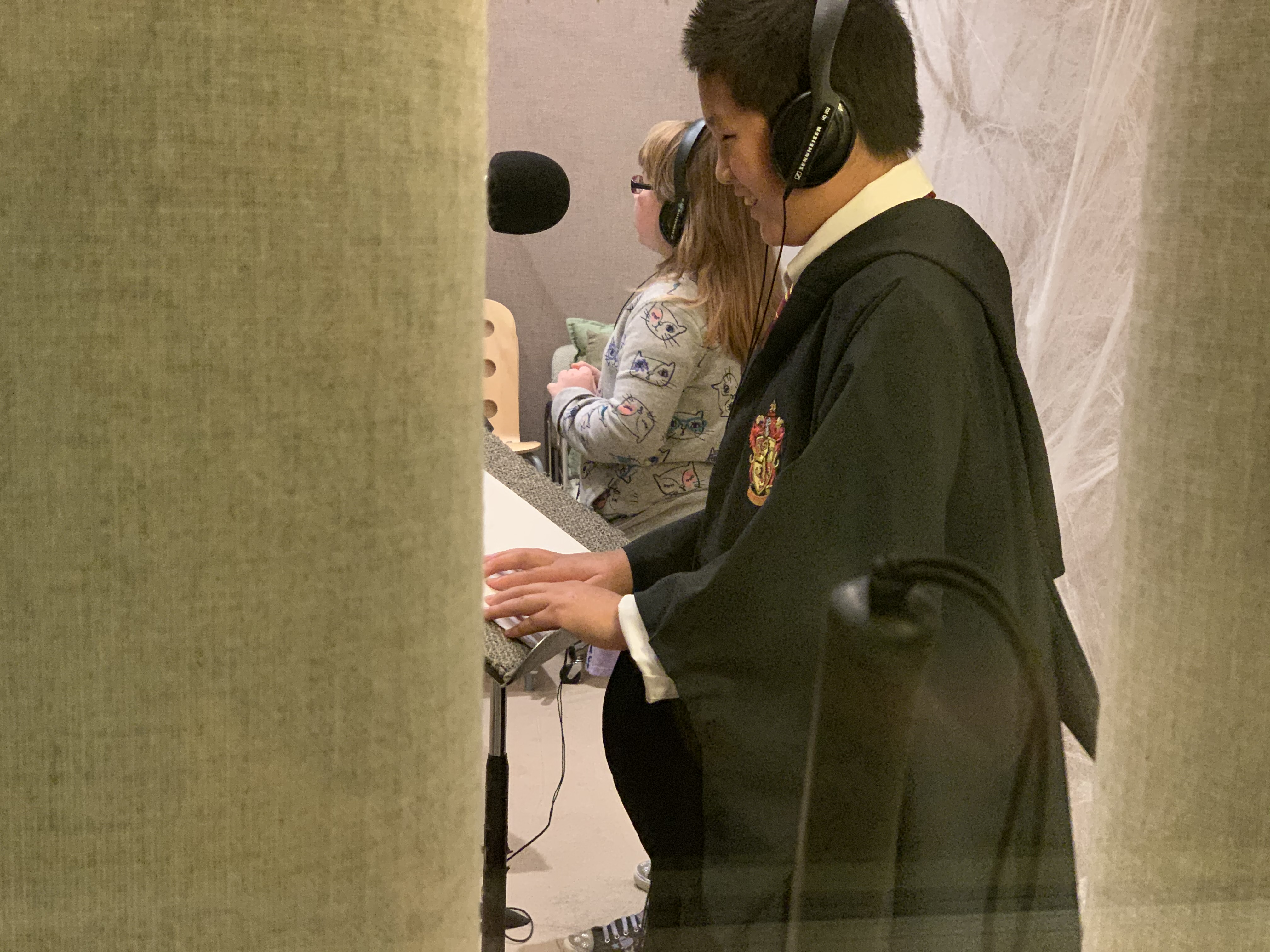 Close-up of two youth patrons speaking into microphones in a recording studio, one reading lines in braille and the other in large print.