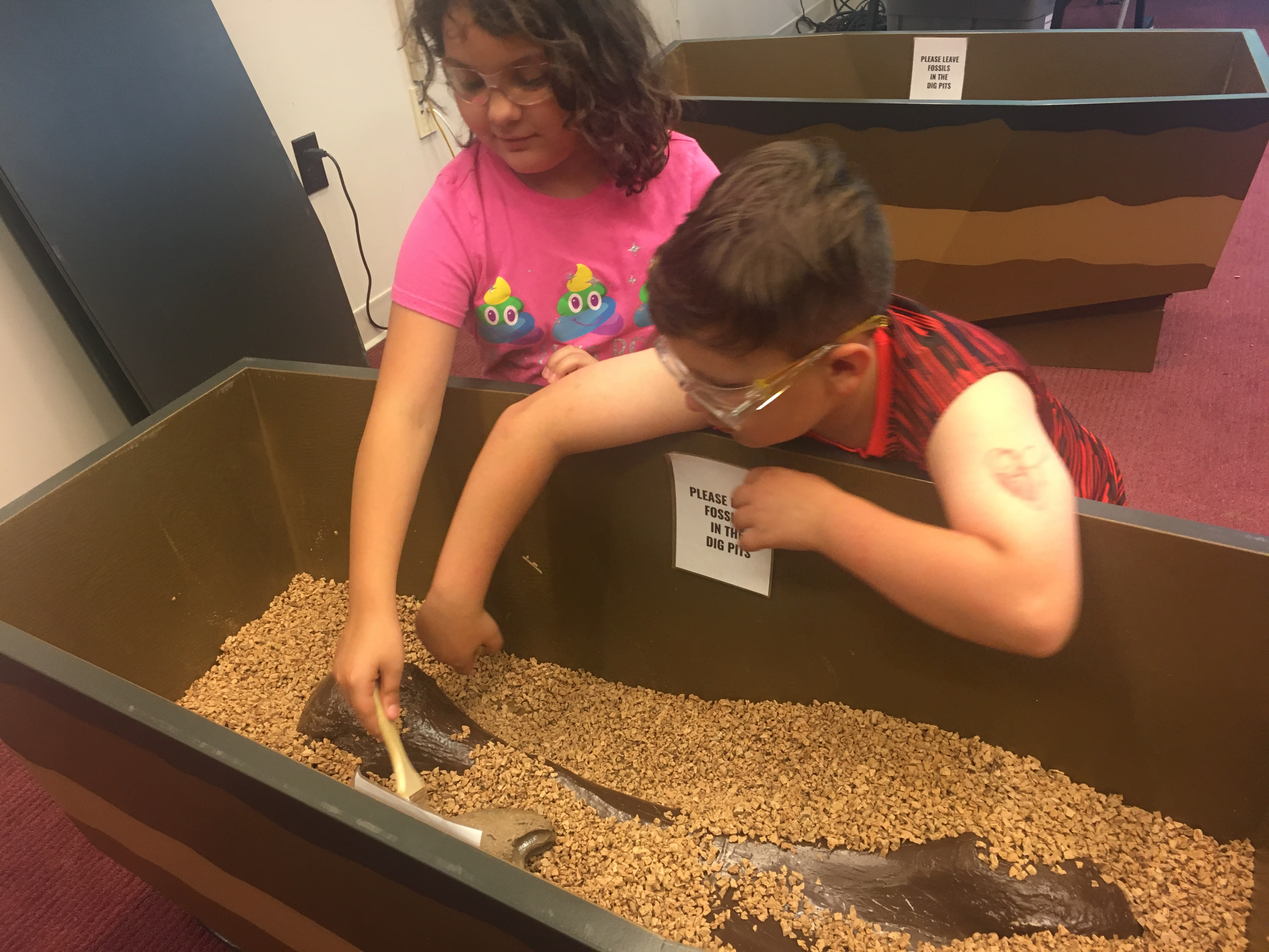 Youth patrons dig in a tub of dirt and sand for a very large fossilized bone.