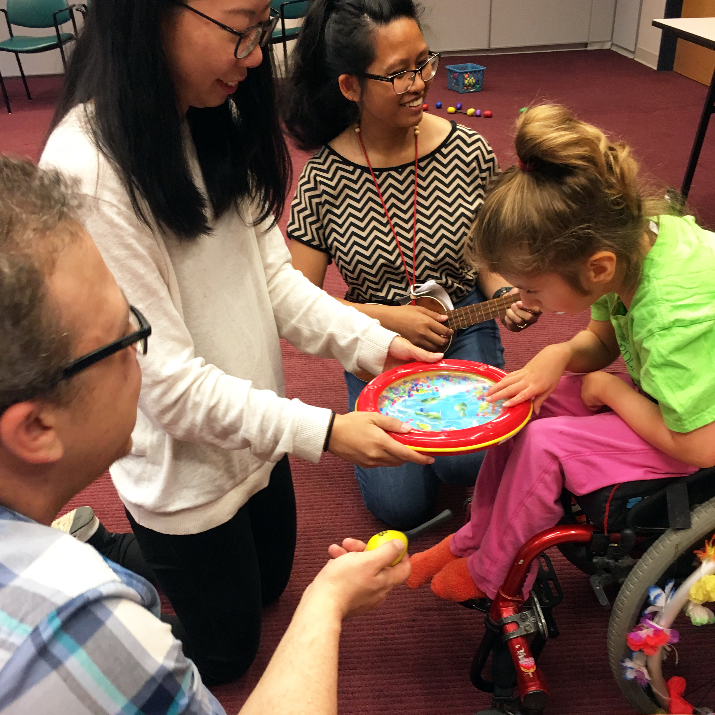 Music Therapy students from SPU play the ukulele, shaker, and sing as a youth patron in a wheelchair focuses on a port-hole toy. The toy has beads in it that, when moved, produce a sound like ocean waves.