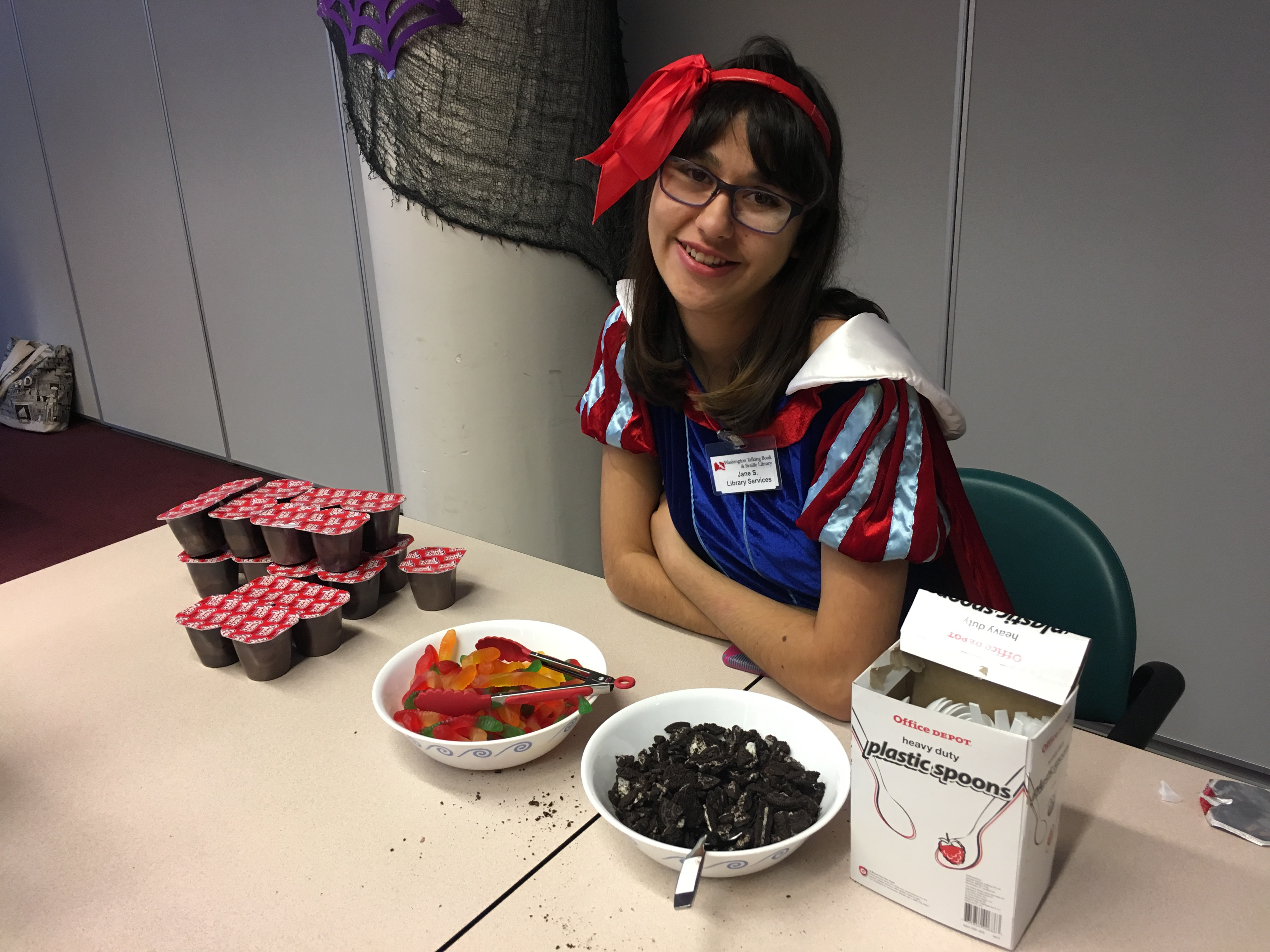"WTBBL Volunteer Jane (dressed as Snow White) works at the ""dirt cup"" station, helping guests mix chocolate pudding, crushed Oreos, and gummy worms for a tasty snack."