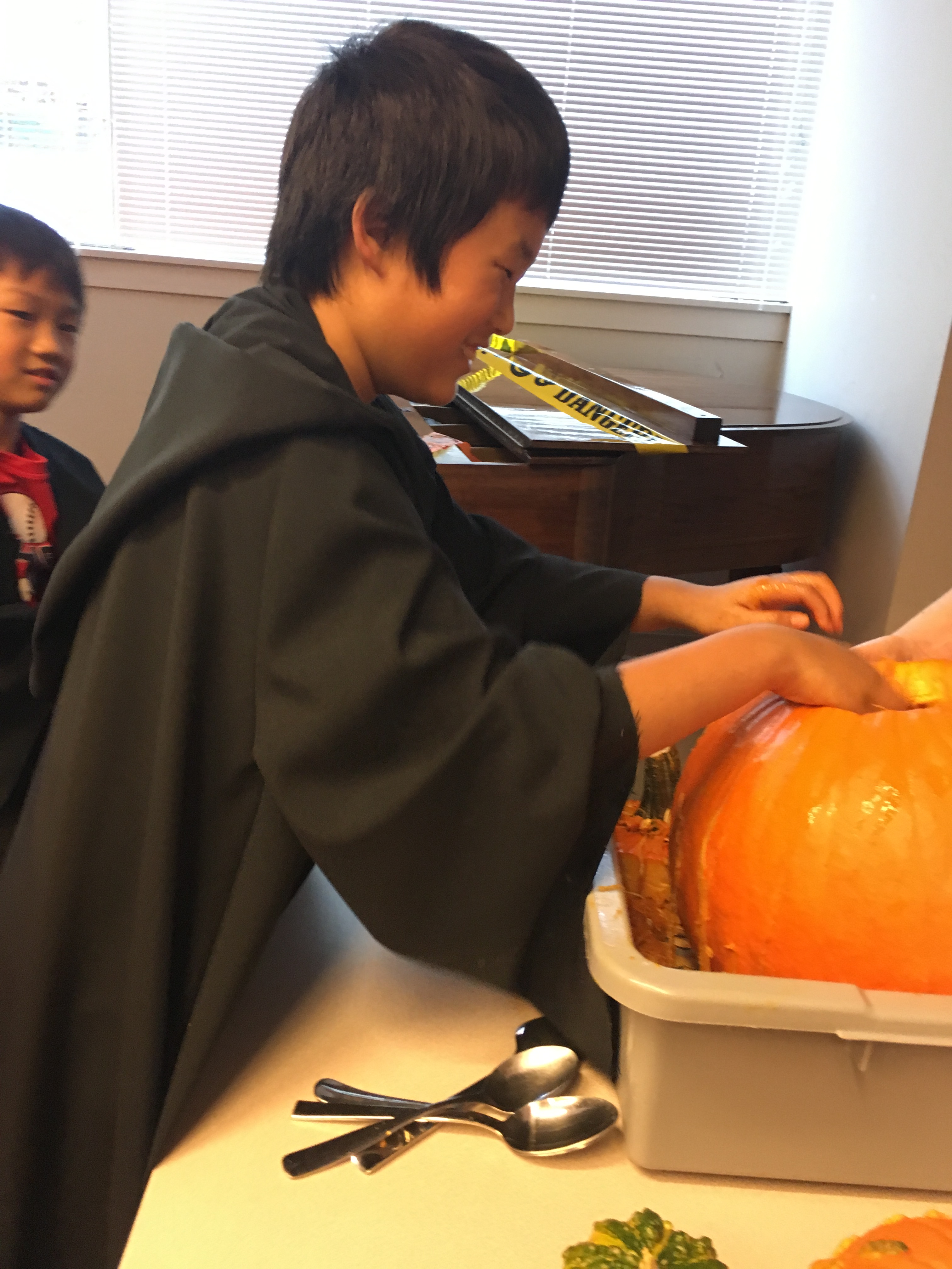 Two children in Hogwarts robes explore the insides of a large pumpkin.