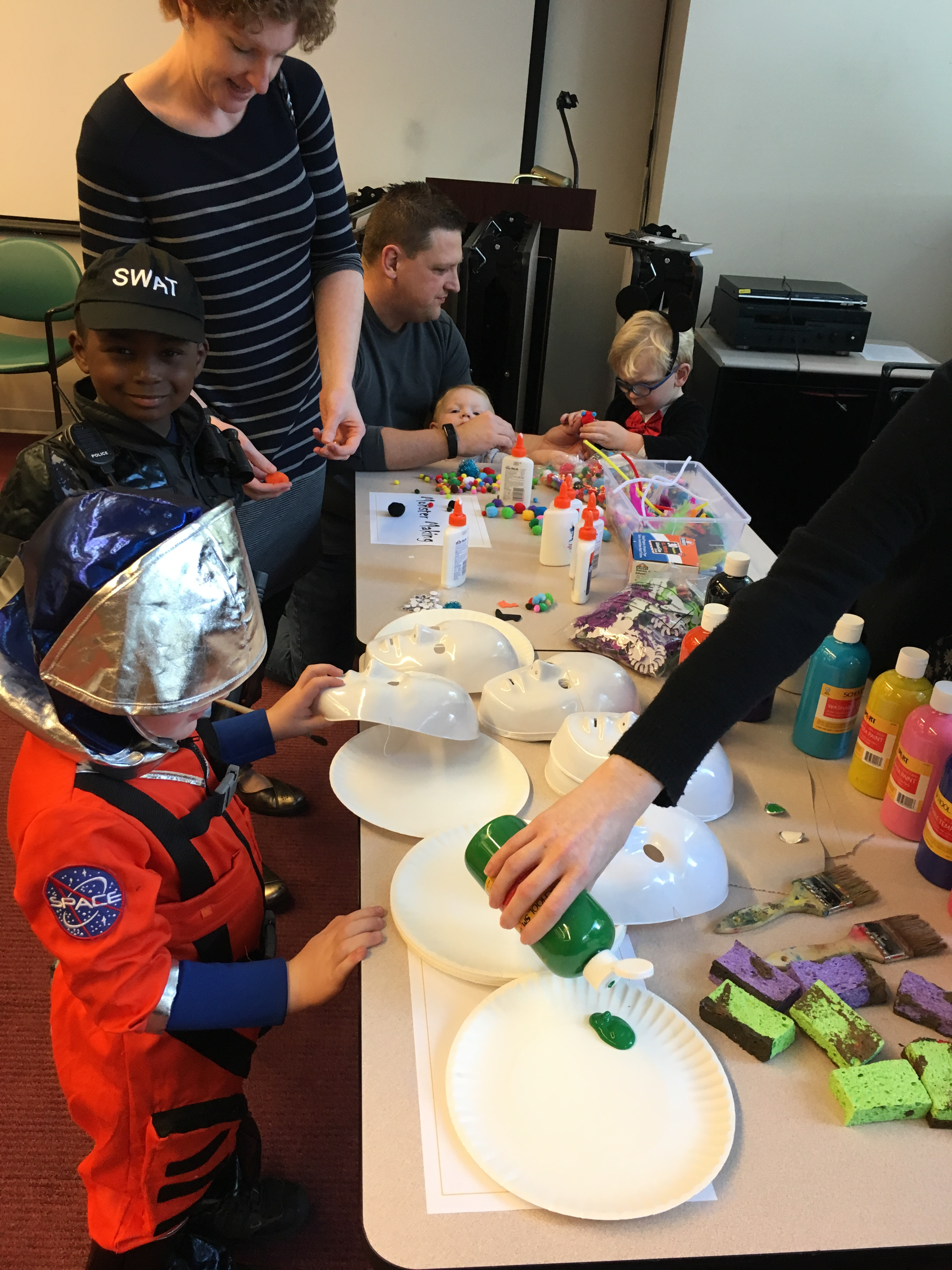 A group of children in costumes (astronaut, police man, Mickey Mouse) paint masks at a craft table.