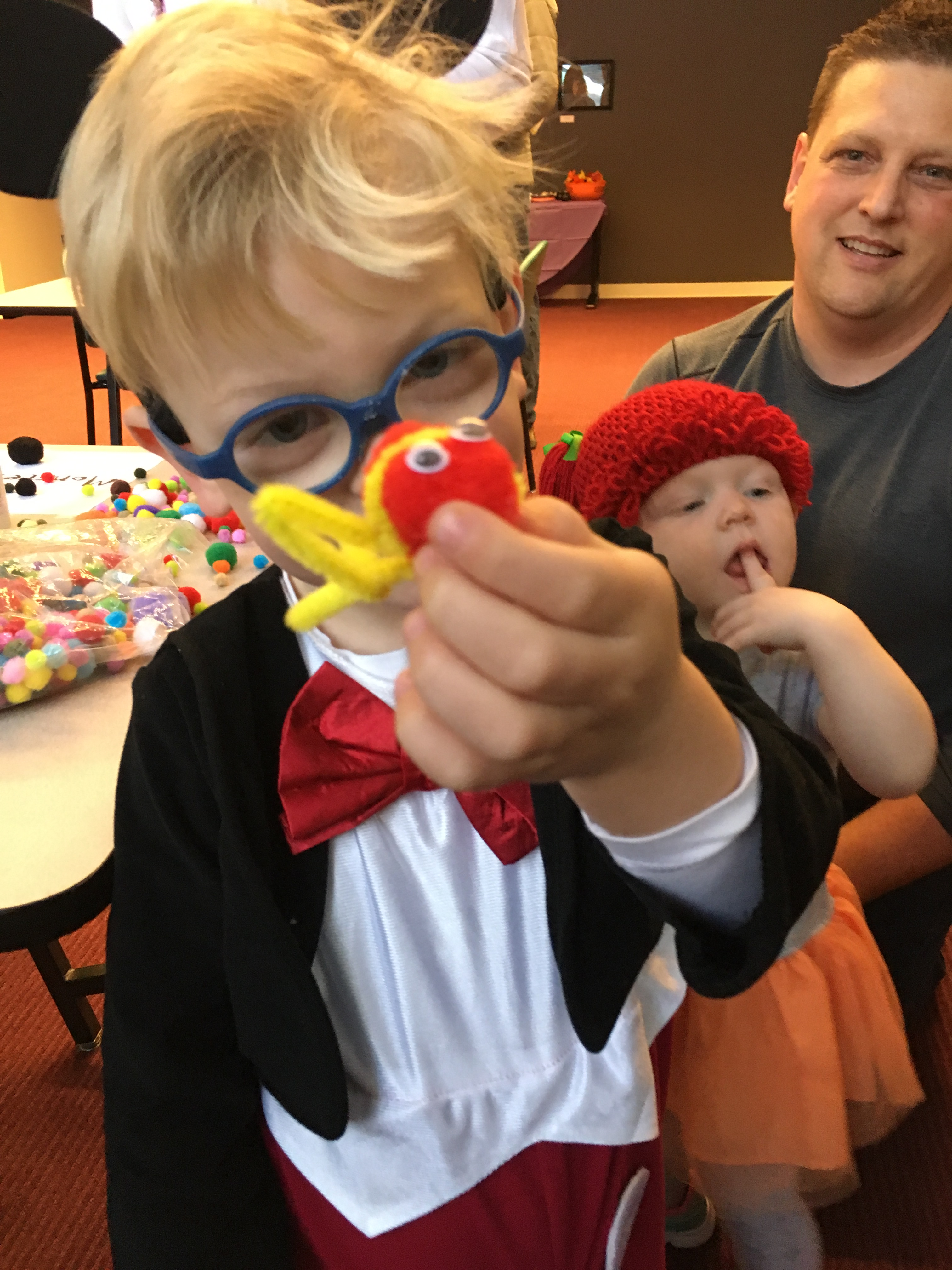 "A child in a Mickey Mouse Costume and glasses holds up a ""monster"" he made out of craft puff balls and googley eyes. His father and baby sister look on in the background."