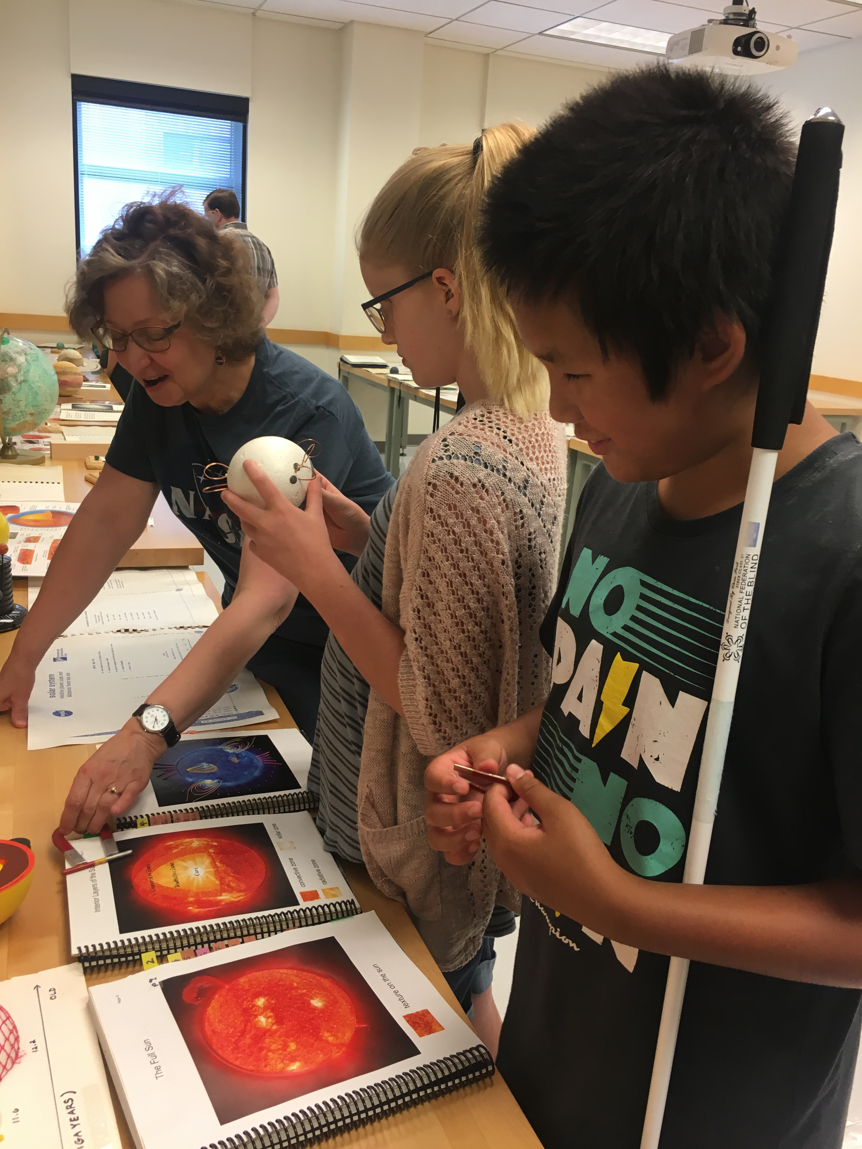 Two youth patrons explore tactile models of the sun and its solar winds at the UW Planetarium.