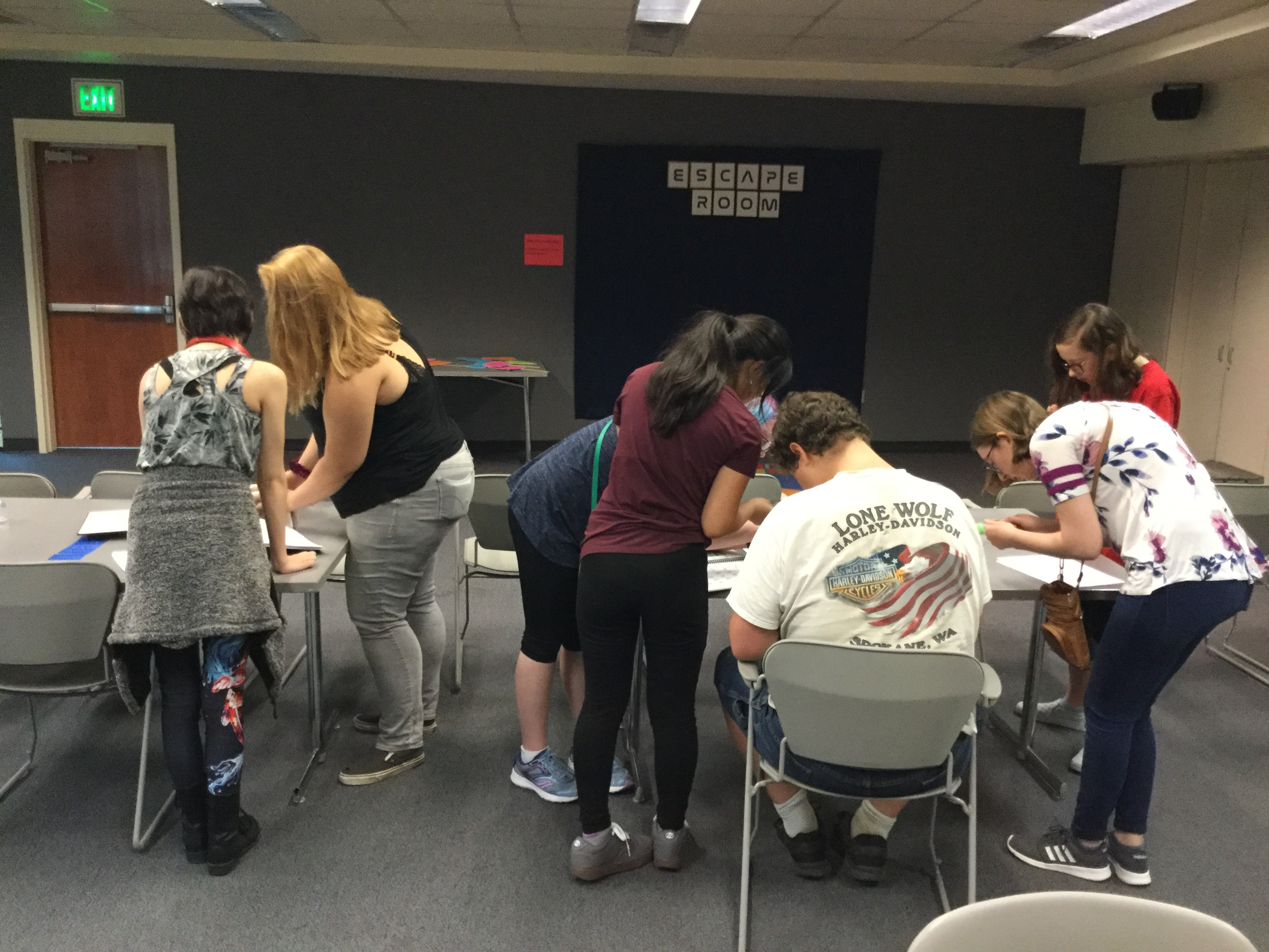A group of teens work together to solve puzzles in the accessible escape room at the Spokane Public Library.
