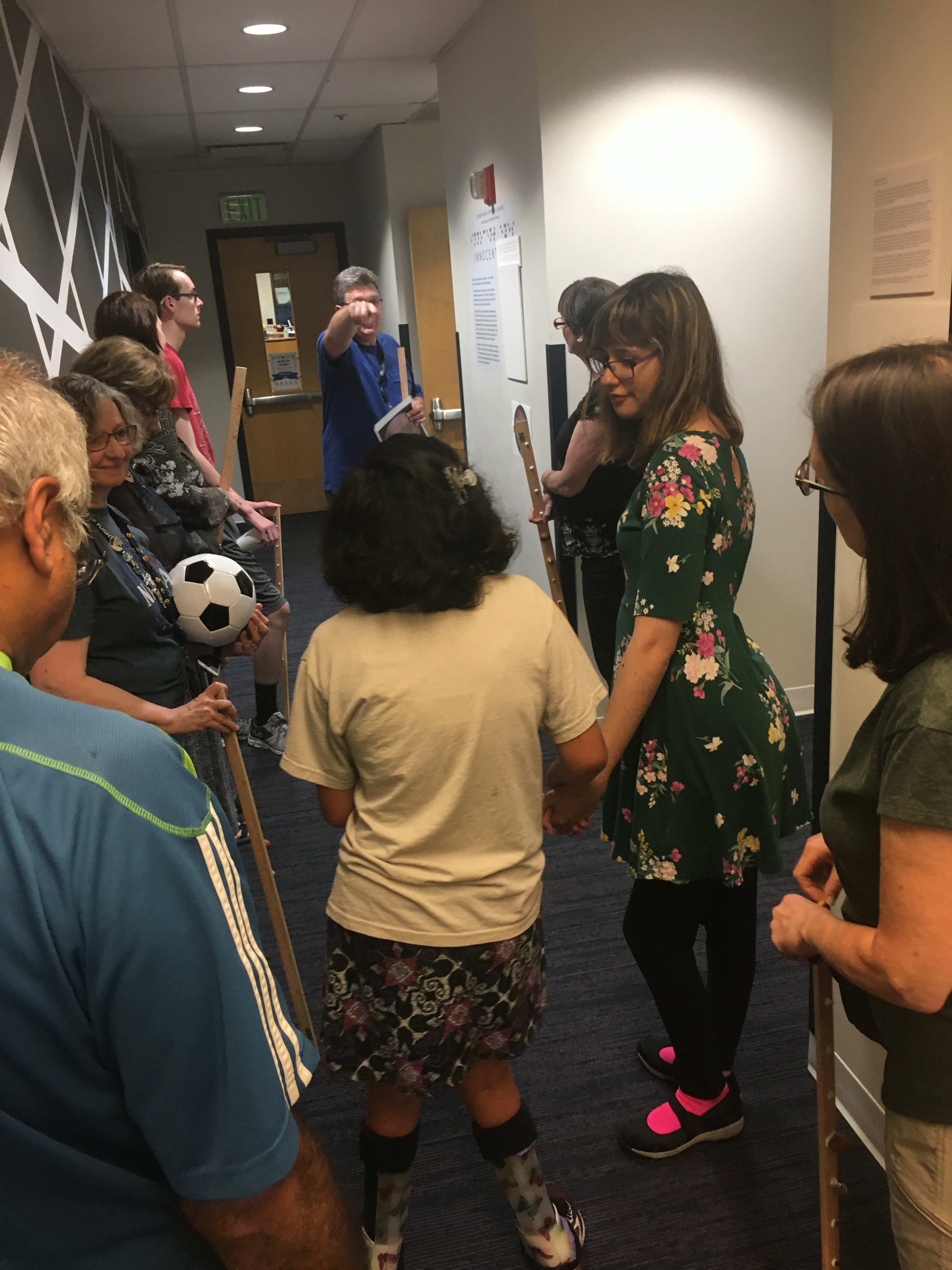 A group of youth patrons and family members walk around WTBBL halls as they go through a scale model of the solar system. One patron holds a soccer ball, representing the size of the sun in relation to each planet (Jupiter is a blueberry).