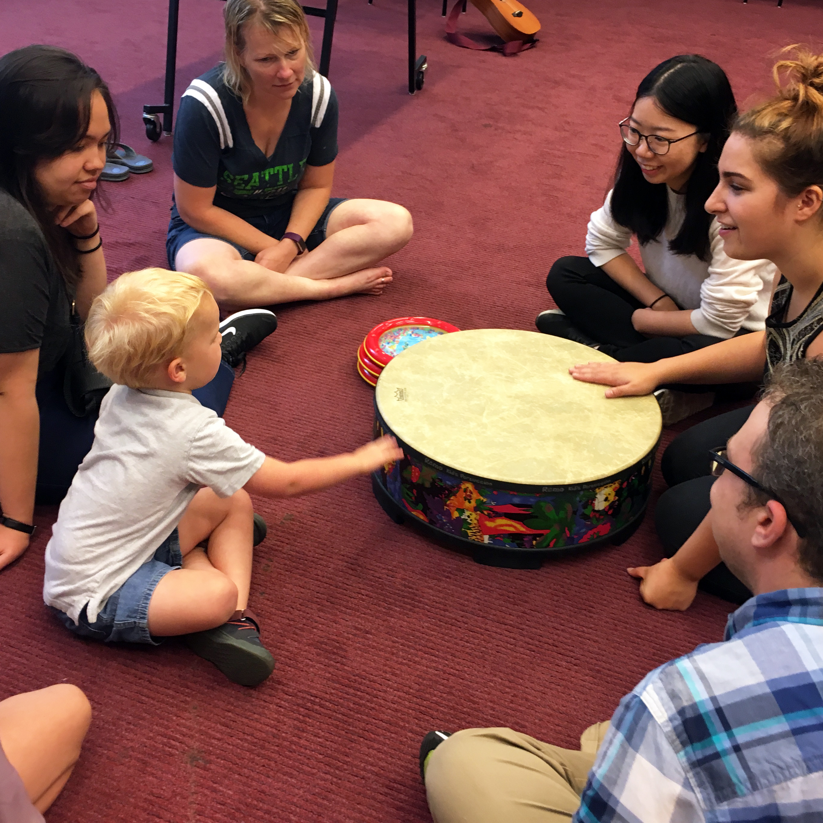 A group of youth patrons and their families sit in a circle around a drum as Music Therapist Dani Valdes leads a song about weather and animal sounds.